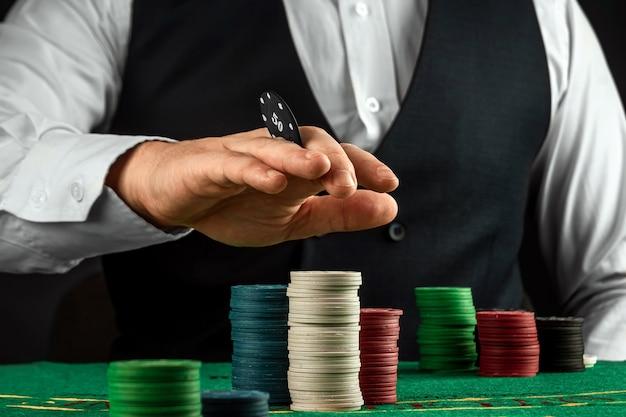 Il maschio passa il croupier in un casinò e gioca i chip su un primo piano del panno verde