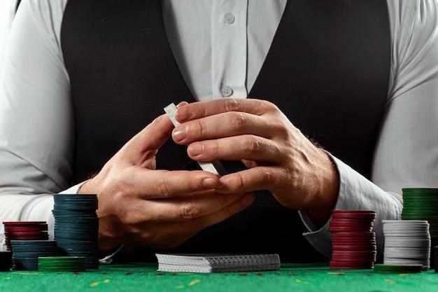 Il maschio passa il croupier mescola il primo piano delle carte