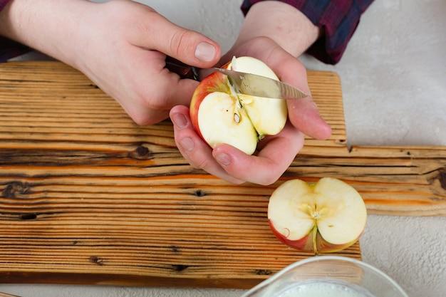 Le mani maschii hanno tagliato una mela a fette