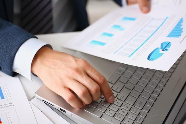 Le mani maschili tengono documenti con statistiche finanziarie
