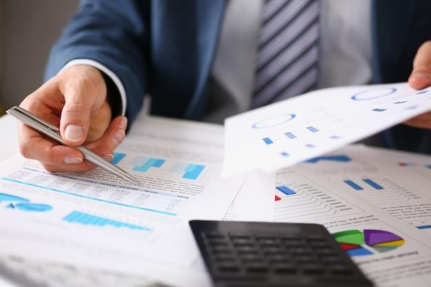 Le mani maschii tengono i documenti con le statistiche finanziarie