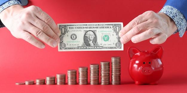 Le mani maschili tengono un dollaro sullo sfondo di pile di monete con salvadanaio di maiale rosso
