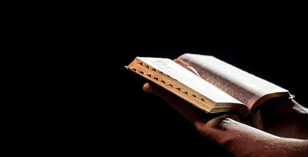 Le mani maschili tengono una sacra bibbia aperta nell'oscurità. il concetto di fede e rapporto personale con dio.