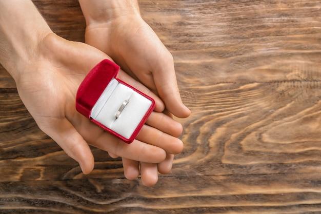 Mani maschii che tengono scatola con anello di fidanzamento sul tavolo di legno