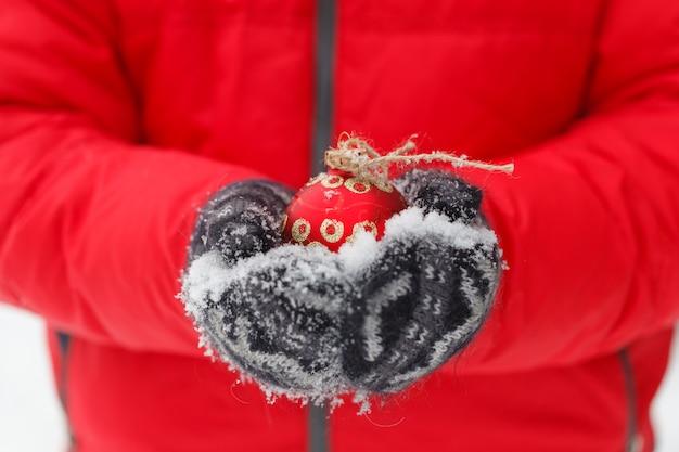 Mani maschili in possesso di una palla rossa di natale. gelida giornata invernale nella foresta innevata. tema di buon natale e felice anno nuovo