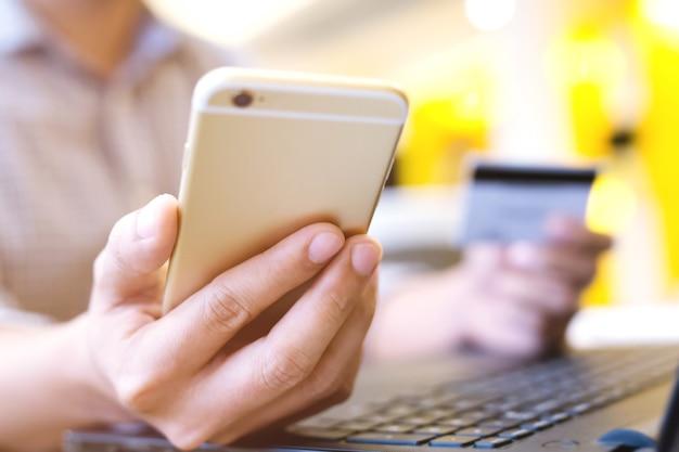 Mani maschii che tengono la carta di credito e utilizzando il telefono e il computer portatile.