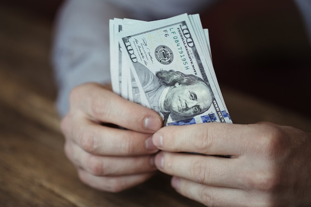 Mani maschii che tengono la banconota del dollaro sulla vecchia tavola di legno