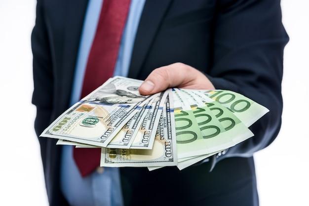 Mani maschili che tengono banconote in dollari ed euro a ventaglio