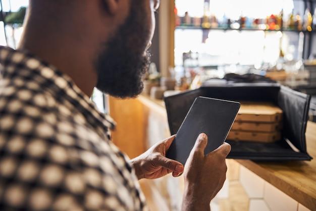 Mani maschili che tengono il pad elettronico del pc mentre il signore in piedi vicino al bancone con scatole per pizza nella borsa per la consegna del cibo