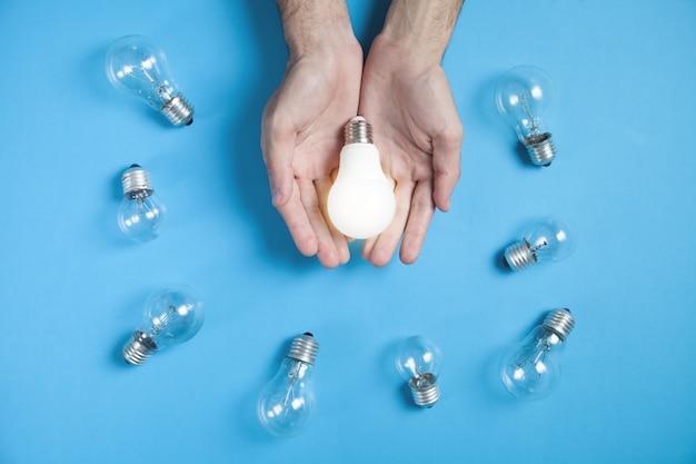 Mani maschii che tengono la lampadina sullo sfondo blu.