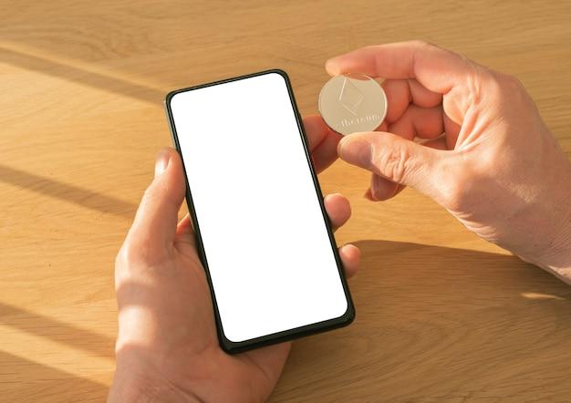 Mani maschili che tengono il telefono cellulare con schermo per mock up e moneta ethereum in mano su un tavolo di legno con luce diurna.