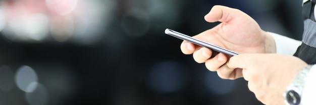 Mani maschii che tengono telefono cellulare