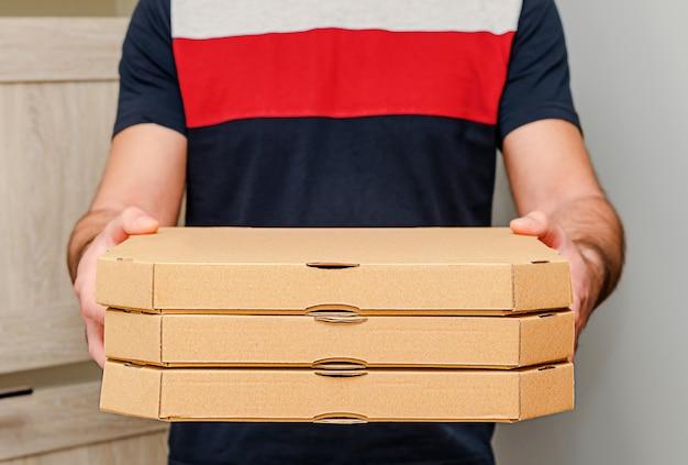 Mani maschii che tengono le scatole di cartone della pizza. servizio di consegna cibo.