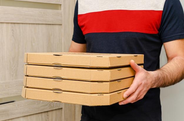 Mani maschii che tengono le scatole di cartone della pizza. ordine e consegna degli alimenti.