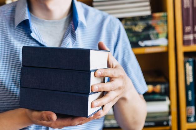 Mani maschii che tengono una pila di libri.