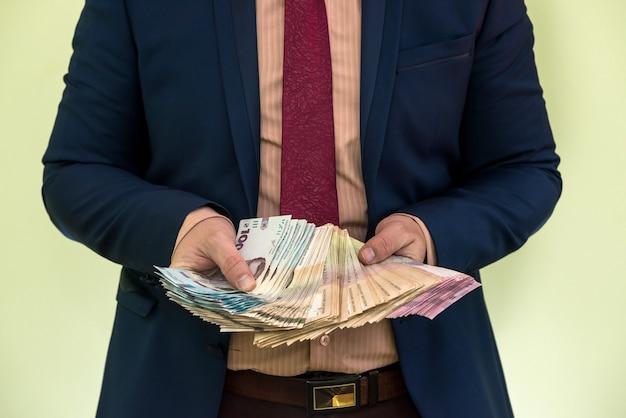 Mani maschili che tengono una pila di banconote di hryvnia ucraine isolate su verde. grivna nuove banconote da 1000 500 e 200 uah. risparmiare denaro concetto