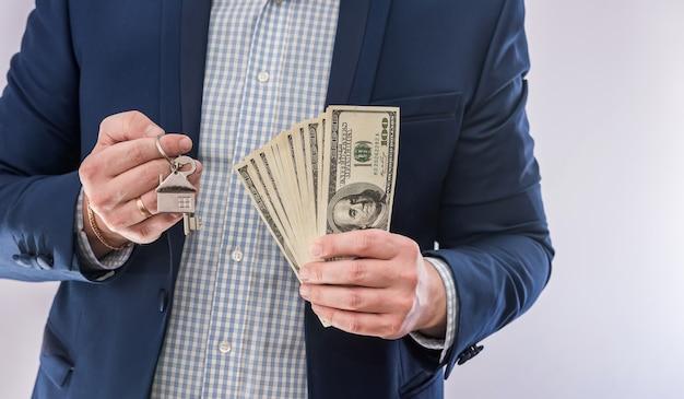 Mani maschili che tengono banconote in dollari usa e chiave di casa isolata. acquisto concettuale o prestito immobiliare