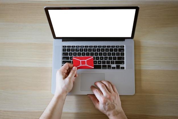 Mani maschii dietro il computer portatile con carta di credito, concetto di acquisto online