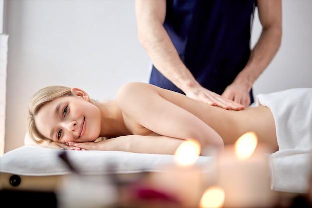 Le mani maschili del massaggiatore fanno un massaggio leggero alla bella donna nella stanza di cosmetologia shi...