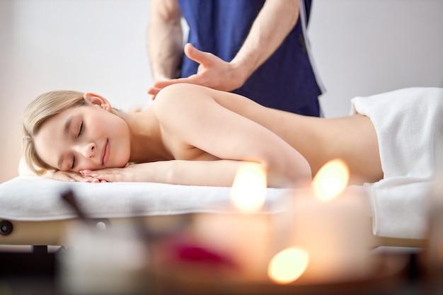 Le mani maschili del massaggiatore fanno un massaggio leggero alla bella donna nella stanza di cosmetologia, rilassata donna caucasica bionda senza camicia sdraiata sulla pancia che ottiene piacere, in camera con le candele