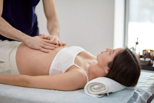 Mani maschili del massaggiatore che fanno un leggero massaggio alla pancia della donna incinta