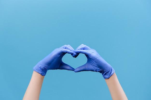 Mani maschili in guanti medici che fanno il simbolo del cuore