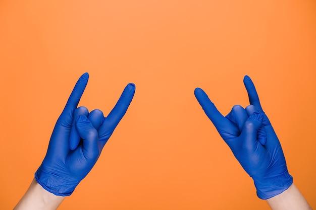 Mani maschii in guanti medicali che fluttuano con gesto di corna