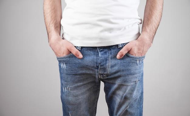Mani maschii in tasca dei jeans su grigio