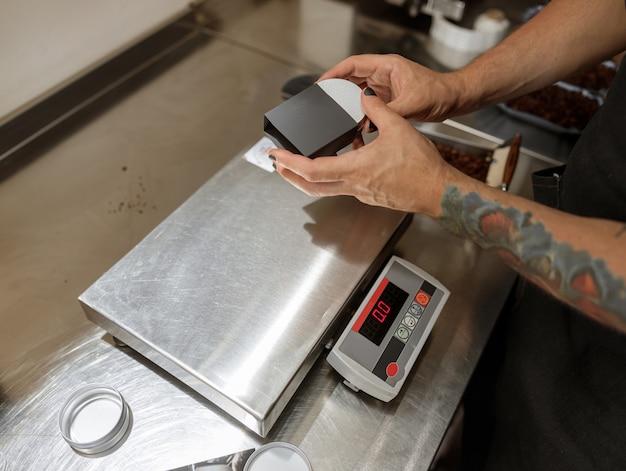 Mani maschili che mettono un barattolo di caffè in metallo nella scatola nera