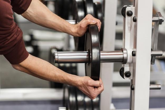 Mani maschii che mettono il piatto del peso sul bilanciere