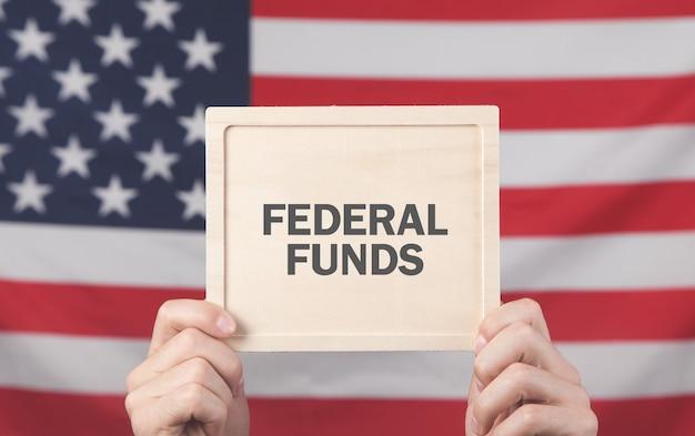 Mani maschii che mostrano il testo dei fondi federali.