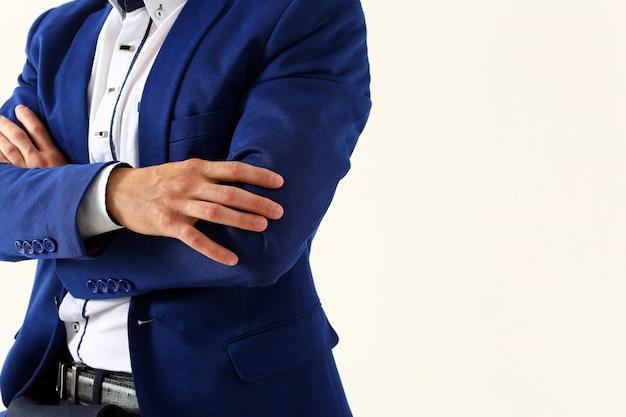 Le mani maschii in vestito hanno attraversato sul primo piano del petto