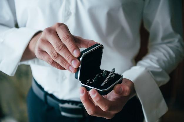 Il maschio passa su una superficie di una camicia bianca, camicia a maniche con gemelli e orologi, primo piano fotografato