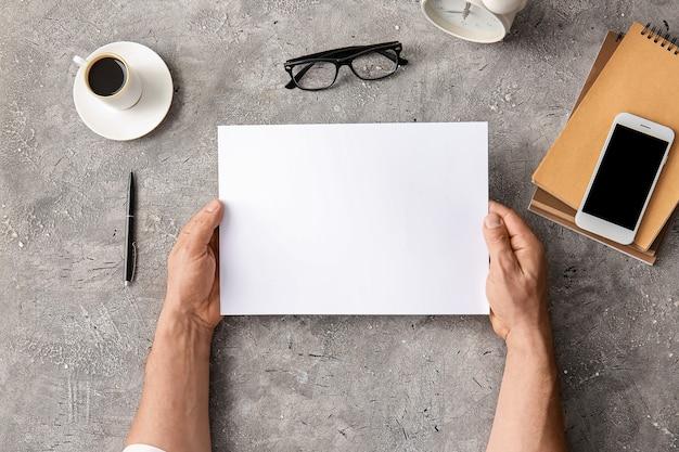 Mani maschili con foglio di carta bianco