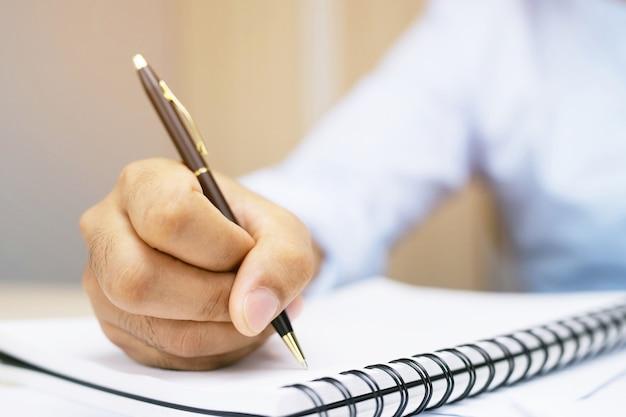 Mani maschii con scrittura della penna sul taccuino