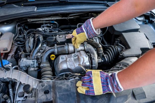 Mani maschili con chiavi. concetto di servizio auto. mani in guanti protettivi contro il motore dell'auto