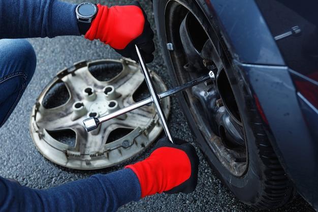 Mani maschii con chiave. uomo che cambia gomma a terra sulla sua auto dopo un incidente stradale