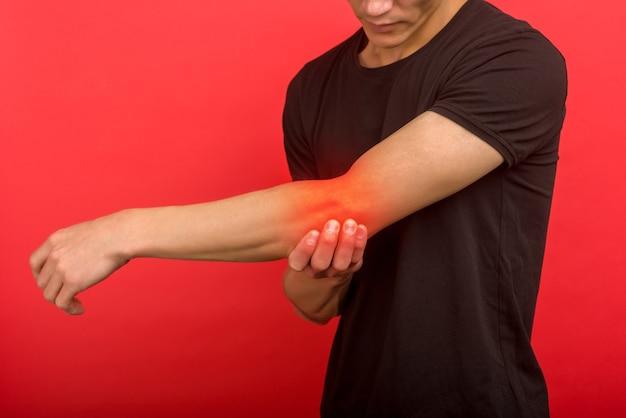 Maschio con dolore al gomito nel braccio ferito sullo sfondo - immagine