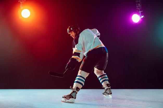 Giocatore di hockey maschio sul campo da ghiaccio e sfondo al neon scuro, sport