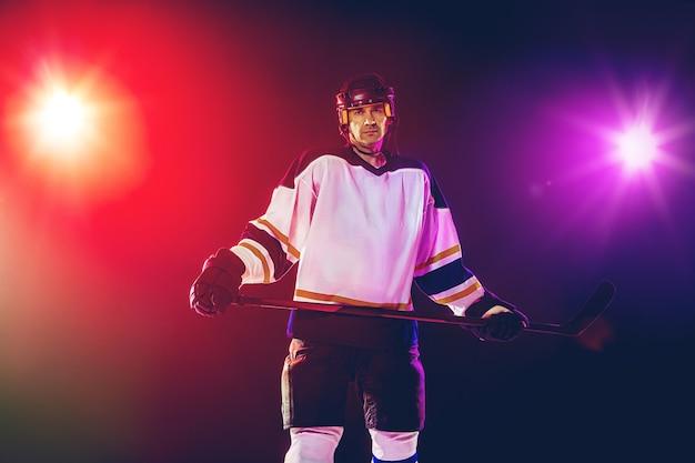 Giocatore di hockey maschio con il bastone sul campo da ghiaccio e la parete colorata al neon scuro
