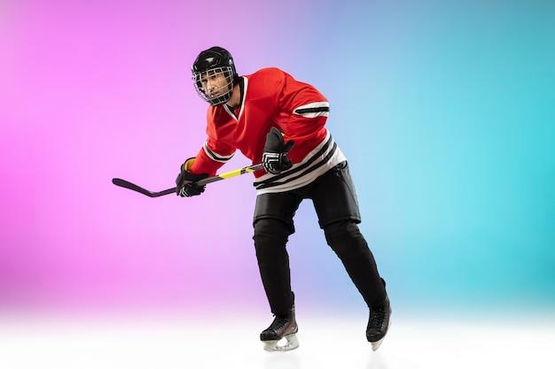 Giocatore di hockey maschio con il bastone sul campo da ghiaccio e sfondo sfumato colorato al neon