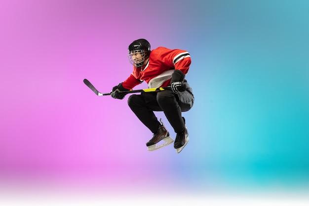 Giocatore di hockey maschio con il bastone sul campo di ghiaccio e parete sfumata colorata al neon