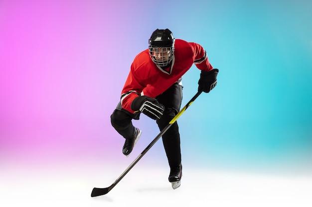 Giocatore di hockey maschio con il bastone sul campo di ghiaccio