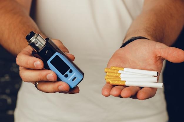 Maschio che tiene sigarette e inalatore vape close up foto