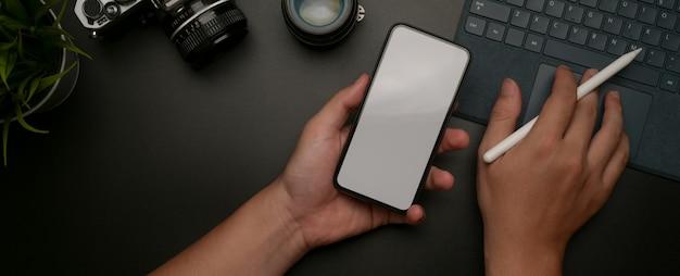 Smartphone maschio del modello della tenuta e lavorare alla compressa digitale sulla scrivania scura