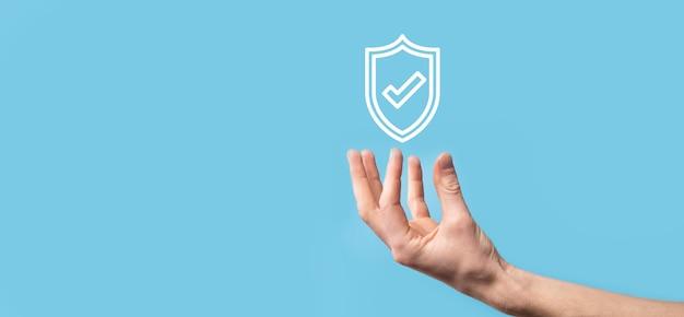 La tenuta maschio protegge lo scudo con un'icona del segno di spunta sulla superficie blu.