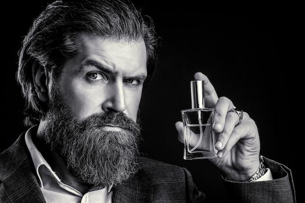 Maschio che sostiene una bottiglia di profumo. profumo uomo, fragranza. bottiglia di profumo o colonia, profumeria, cosmetici, bottiglia di colonia profumata, colonia di contenimento maschile. bianco e nero.