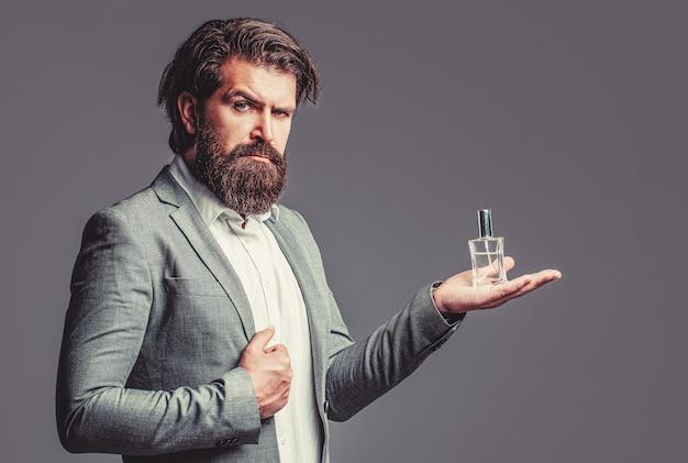 Maschio che sostiene una bottiglia di profumo. profumo uomo, fragranza. profumo o bottiglia di colonia e profumeria, cosmetici, bottiglia di profumo, colonia maschile. profumo maschile, uomo barbuto in completo.