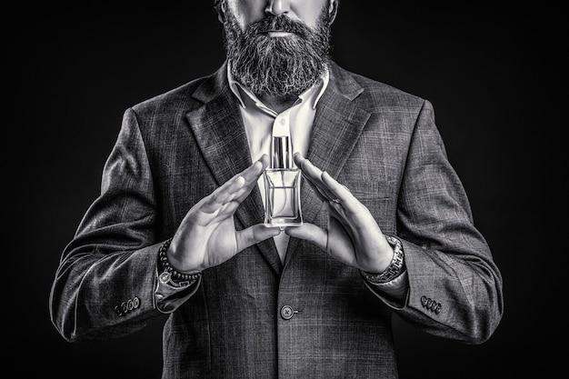 Maschio che sostiene una bottiglia di profumo. profumo uomo, fragranza. profumo o bottiglia di colonia e profumeria, cosmetici, bottiglia di profumo, colonia maschile. profumo maschile, uomo barbuto in completo