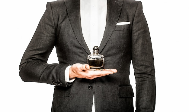 Maschio che sostiene il profumo della bottiglia profumeria bottiglia di profumo o colonia